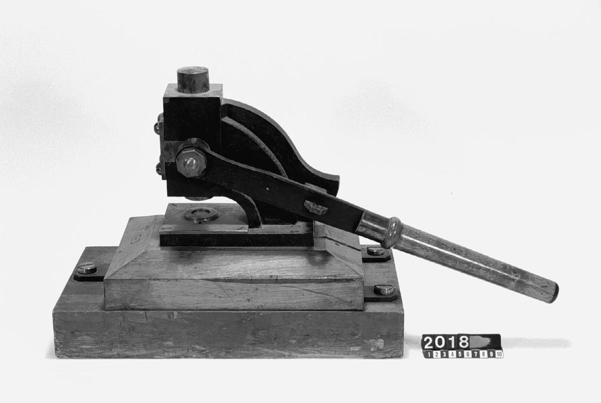 """Stämplingspress med excentrisk skiva och hävstång. Text på föremålet: """"F-a-E-5 XIII. ?""""."""