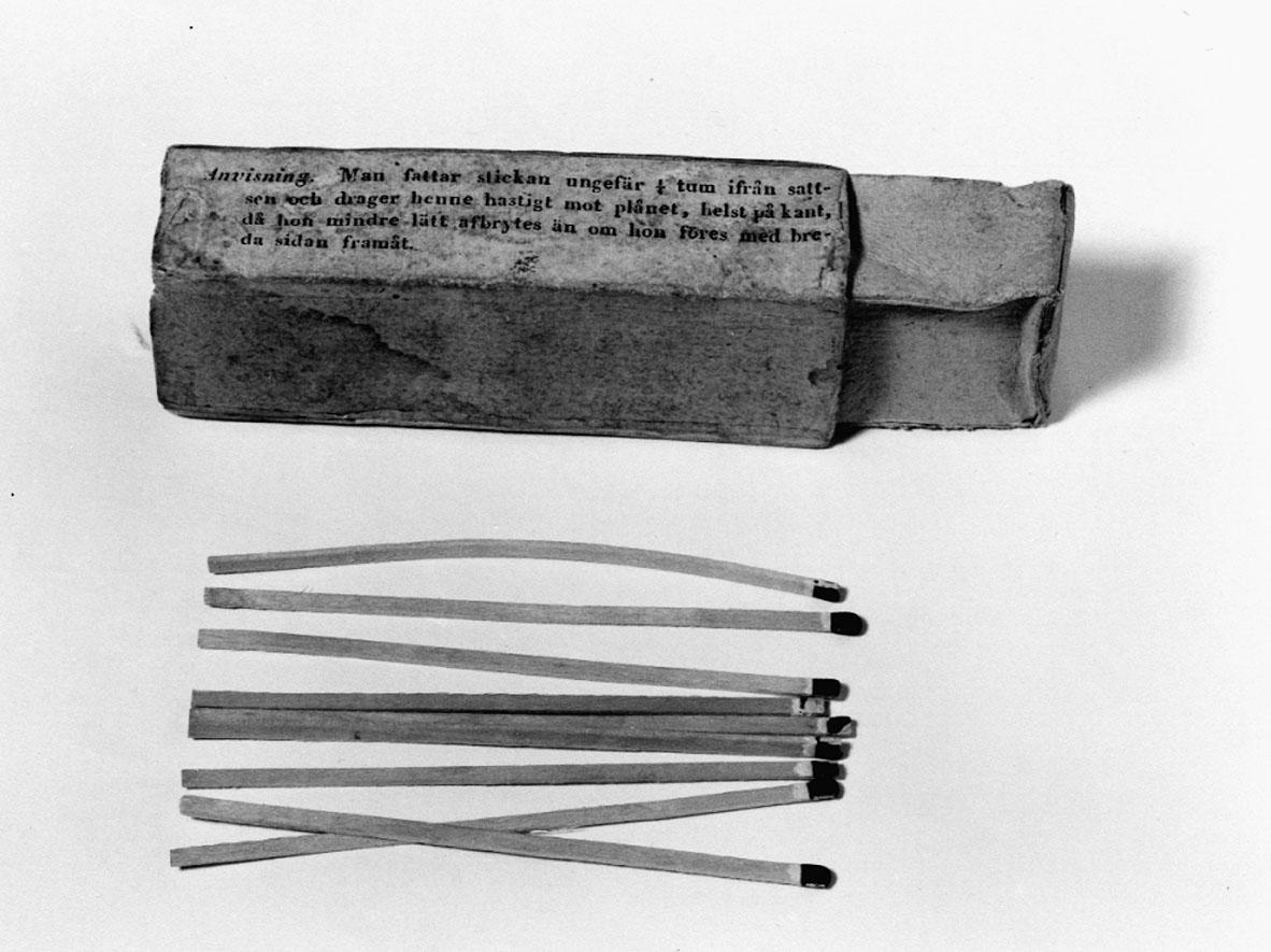 """Strykstickor  utan fosfor, i ask.  """"Patenterade Strykstickor utan fosfor, tillverkade, vid J.S. Bagges & C:o Kemiska Fabrik i Stockholm"""".  """"Anvisning. Man fattar stickan ungefär 1/4 tum ifrån satsen och drager henne hastigt mot plånet, helst på kant, då hon mindre lätt afbrytes än om hon föres med breda sidan framåt"""". Enligt patent 1845-10-30 för Gustaf Erik Pasch på strystickor med sats av kaliumklorit, plån med rödfosfor och svavelantimon. Askens längd: 84, bredd: 33 och höjd: 20 mm."""