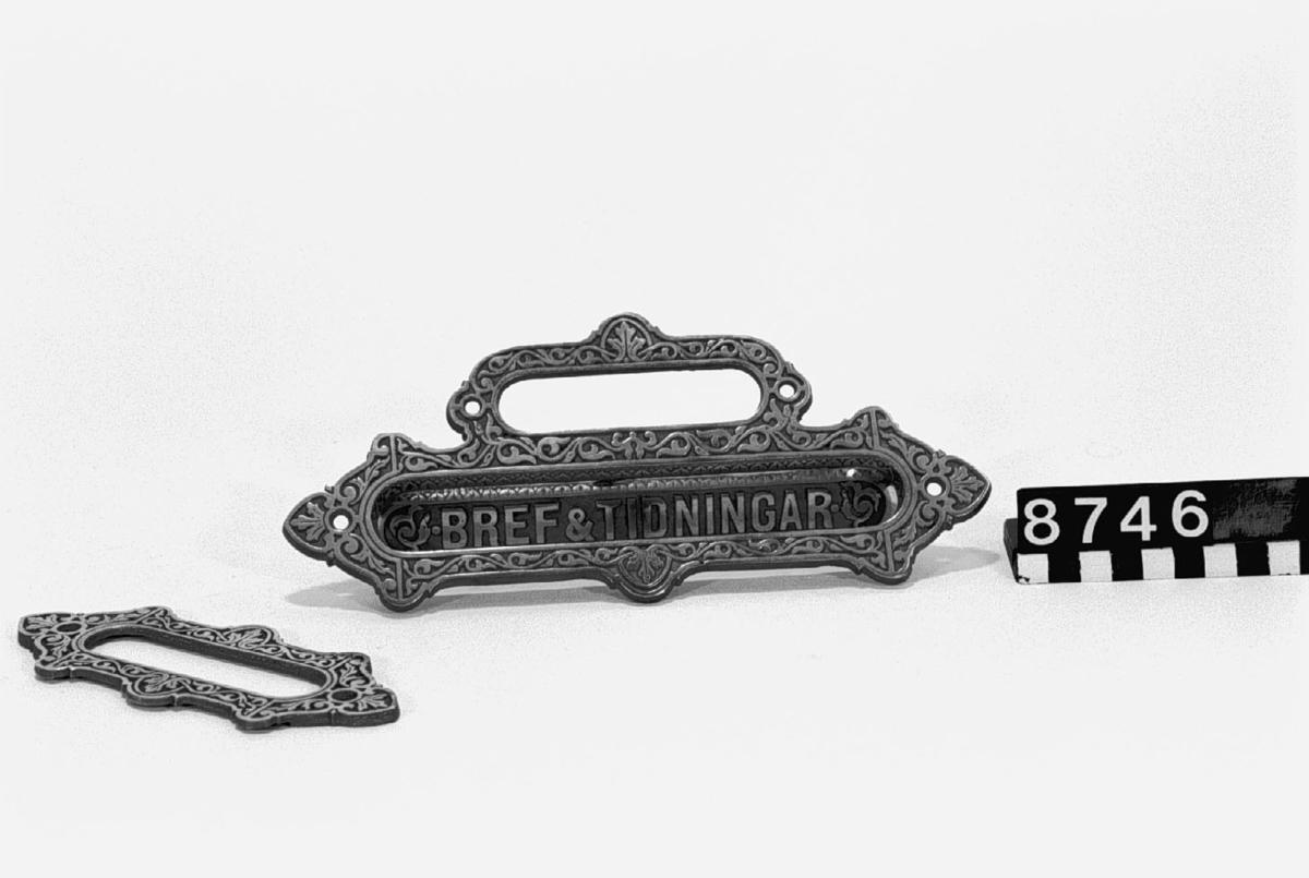 """Brevlådbeslag och ram för namnskylt av förnicklat gjutjärn. På brevlådbeslag:""""BREF & TIDNINGAR"""" och stempel """"E"""" under krona. K.T.H. samling."""