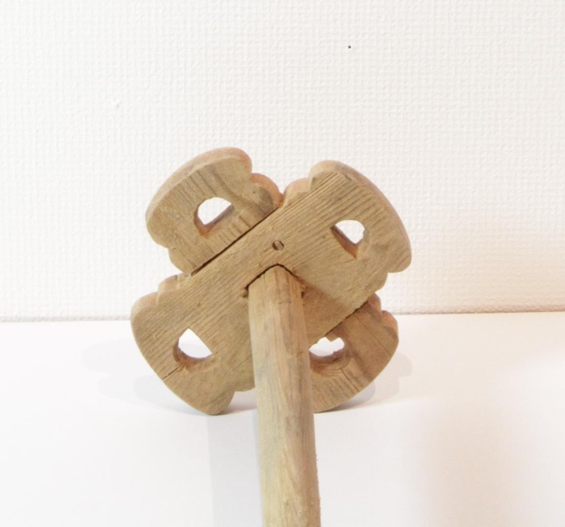 Kinnestav med langt håndtak som er rundt i snitt og smalner litt mot enden. I andre enden er det festet et vannrett stående kryss som består av to deler som er plugget fast til hverandre. I hvert av kryssene er det skåret et gjennomgående hull. Kryssene er profilerte. Kinnestaven hører til en stavkinne som ble brukt til å kinne smør med.
