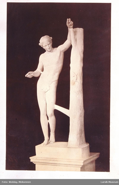skulptur av mann stående ved trestamme, firfisle