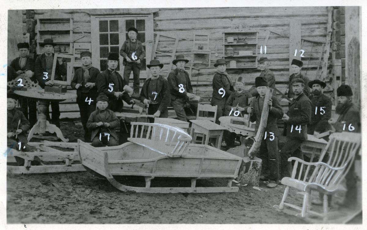 Bildet viser 16 menn og gutter oppstilt utenfor en tømmervegg. Alle holder et verktøy i hånda og de står mellom stoler, bord, kjelke og krakker. Alt er snekra. Dette er fra ei snekkerskole i Lomen, Vestre Slidre.