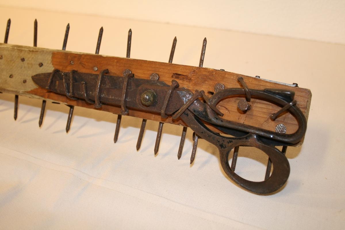 Sengeben i tre med detaljer av jern: saks, beslag samt en mengde lange spiker.