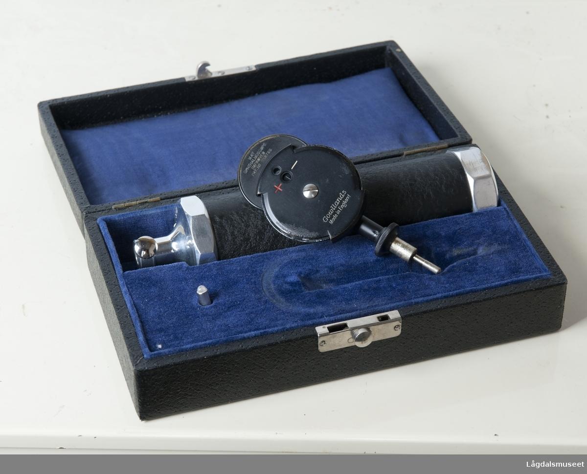 """Ophthalmoscopet ligger i et etui som er formet slik at instrumentet får fast plass. Etuiet er rektangelformet, det er lokk og det er plass til den ytterste delen som brukes til å se inn i øyet. Selve hoveddelen har en bryter av/på, inne i skaftet til hoveddelen er det plass til batteri som festes med skrulokk. Det er et eget rom til pære i etuiet. Pæren ligger i dette rommet. Etuiet er sort trukket med preget papir (imitert skinn), inne i etuiet er lokket trukket med silke, etuiet (innvendig) er fløyel. Ophthalmoscopets hoveddel er svart, trukket med imitert skinn, metalldelene er blanke. Den ytterste delen er svart bakelitt med noen små detaljer i blank metall. Denne delen har noen regulerbare deler/skiver. Hengslene og låsen er blank metall. Inne i etuiet er det en etikett hvor det står """"To prevent corrosion of the hanlde the battery should be removed when exhausted"""".  Hoveddelen har inskripsjonen """"Gowllands Made in England"""".  Den ytterste delene har inskripsjonen """" May Ophthalmoscope improved Pat.no. 358766"""". Nederst står det """"Gowllands Made in England""""."""