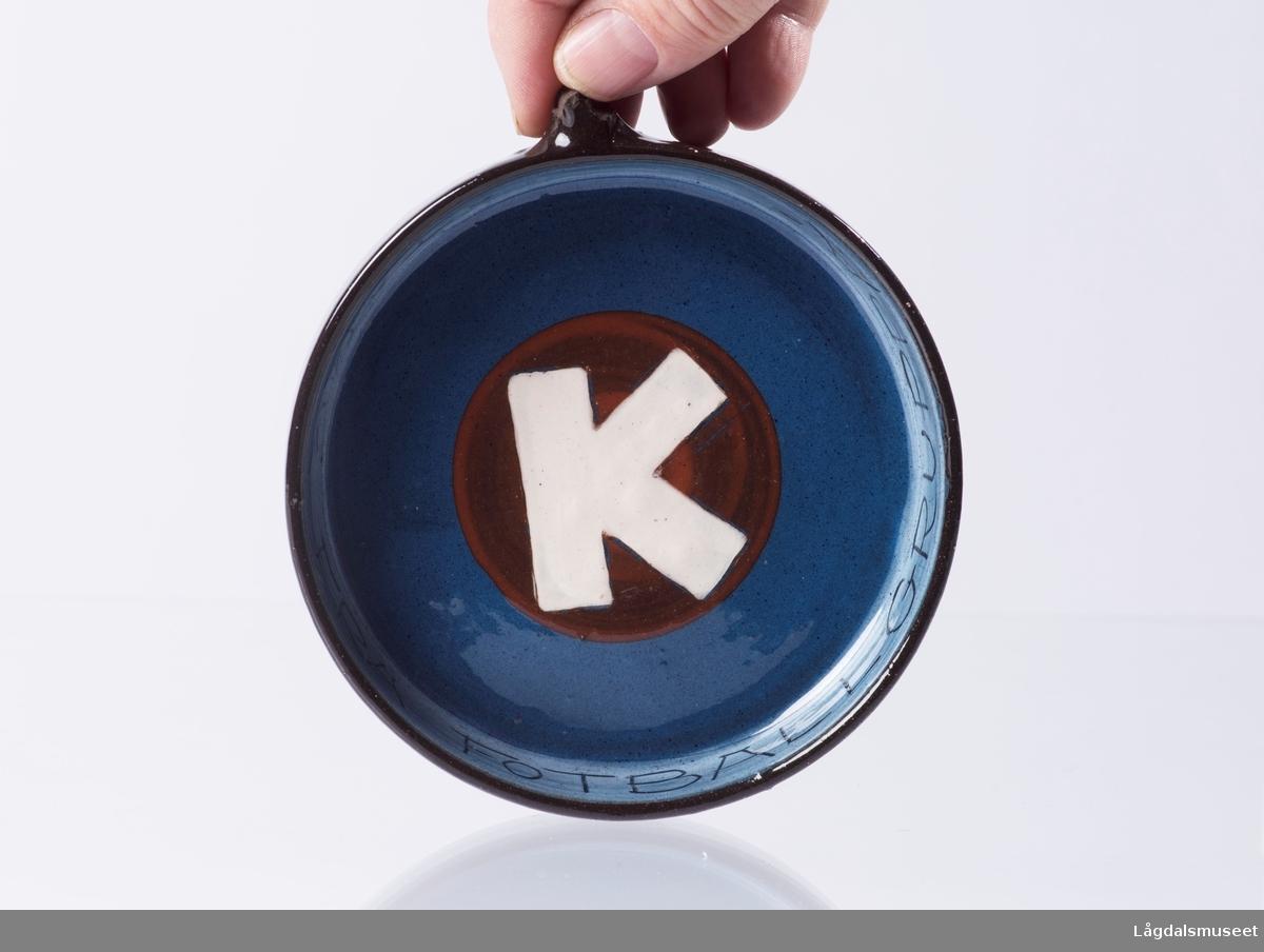 """Motivet i midten av panna viser Kongsberg Idrettsforenings logo (K). Langs kanten på innsiden er det skrevet """"TAKK FRA FOTBALLGRUPPA""""."""