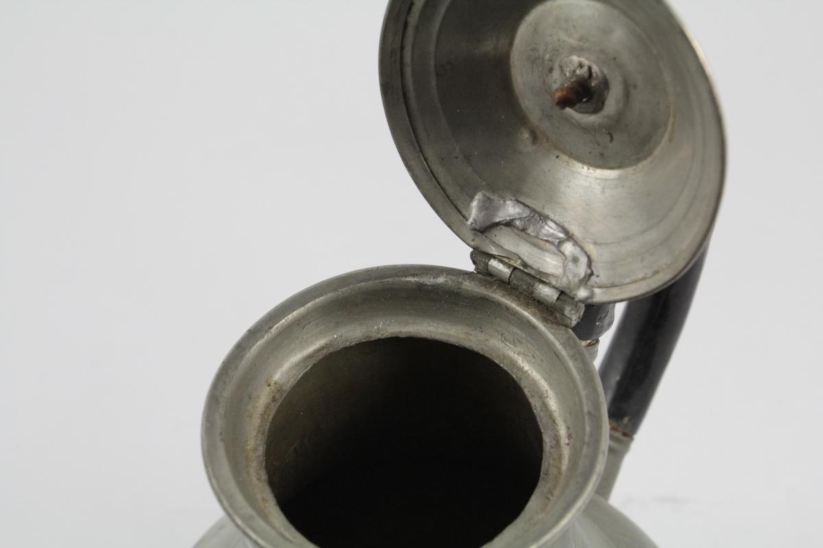 Balusterformet, korpus, S-svungen tut med langsgående rifler, hanken C-formet av sort tre, lokket hverlvet med sort knapp.