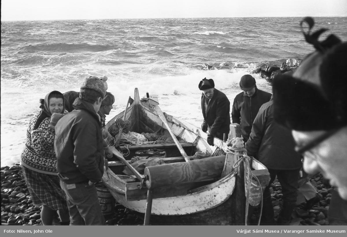Brødrene Andersen fått hjelp til å dra båten på land. Bildet er tatt i Gurluovttgohppi / Godluktbukt. Den unge mannen nærmest til venstre er en Johansen fra Mortensnes og kvinnen med ansiktet hitover er Johanne Pettersen. 28. februar 1967.