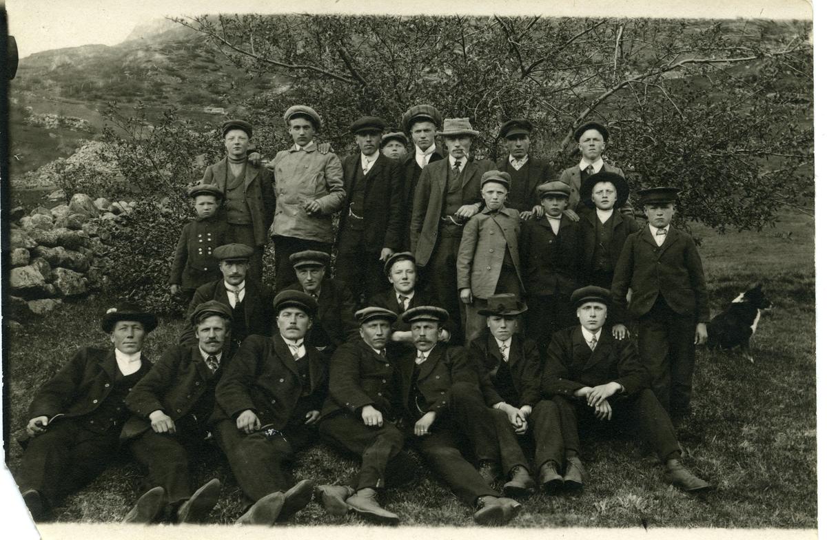 Bilde av flere menn samlet foran et tre. Bildet er tatt ved en basar ved Nedre Dalen skule i Vang kommune i Valdres. Bildet er tatt ca 1908-1910.