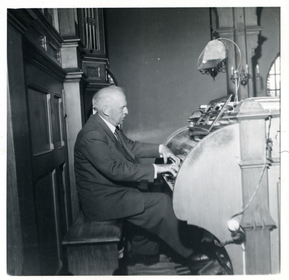 Portrett av en eldre mann som spiller på et orgel. Mannen er iført dress og slips.