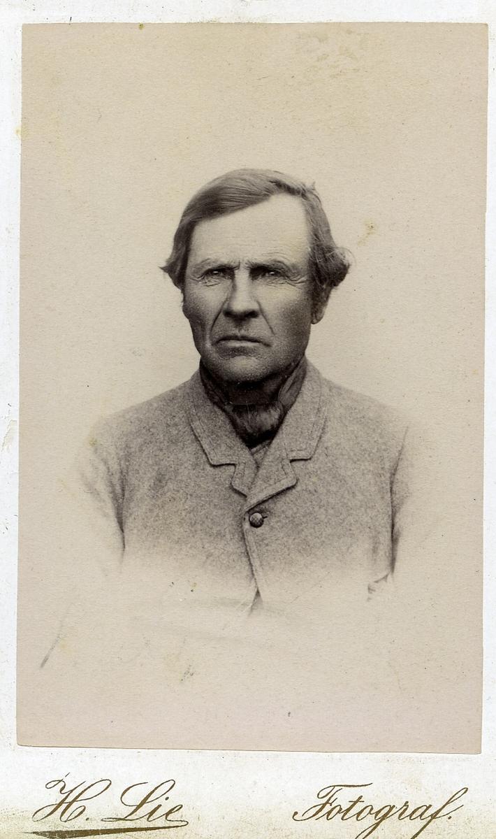 Portrett av mann iført halstørkle og jakke.