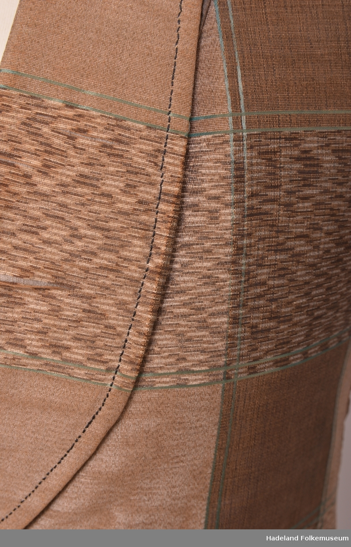 Vest herre. Brun/beige/grønn mønstret. Kort modell. Bomullstoff i lerretsbinding. Forskjellig farge på innslag og renning for mønstret effekt. Små stofftrukne knapper i front. Ryggen har blank lin.stoff Fóret med naturfarget linstoff i lerret. Langt slag på kragen. Hempe bak til stramming.