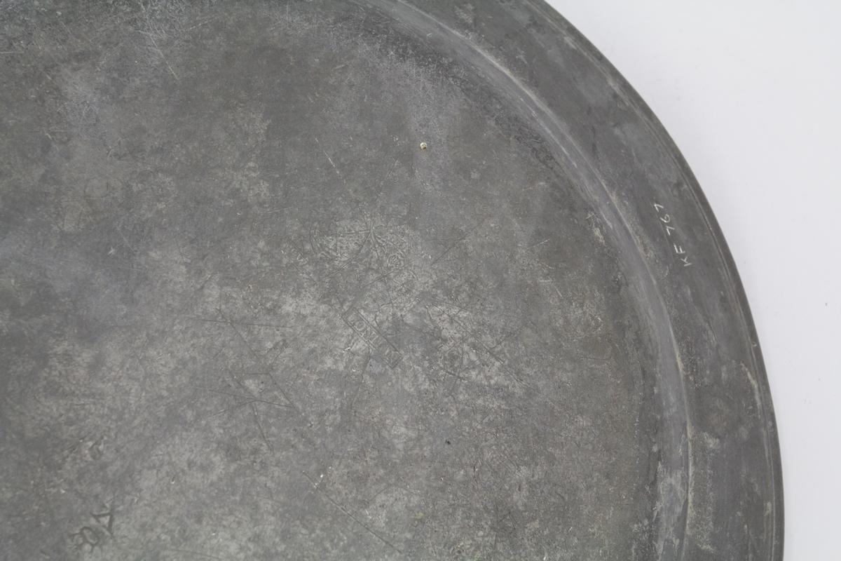 Flatt, sirkelrundt, markert svakt, skrånende glatt kant. Stemplet på baksiden.
