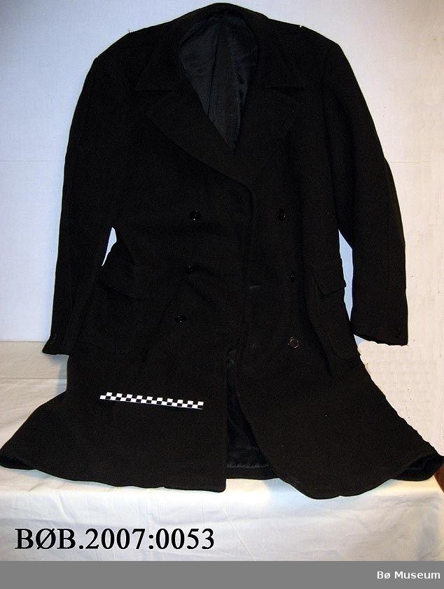 Skreddersydd herrefrakk med skulderputer og innapålomme. Frakken har 2 lommer med klaffar. Frakken er både høgre og venstreknept. 3 store knappar på kvar side. 2 små knappar på kvart erme.