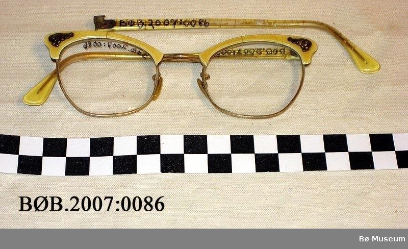 Damebriller i metall og plast med ein liten krusedull på kvar side til pynt.