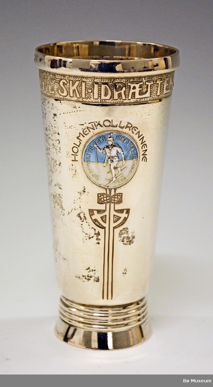 """Sølvpokal med merke i blått foran. Merket har følgende innskrift:  """"Foreningen til Ski-idrættens Fremme 1883"""" Rundt dette merket står: """"Holmenkollrennene"""" (u årstall)"""