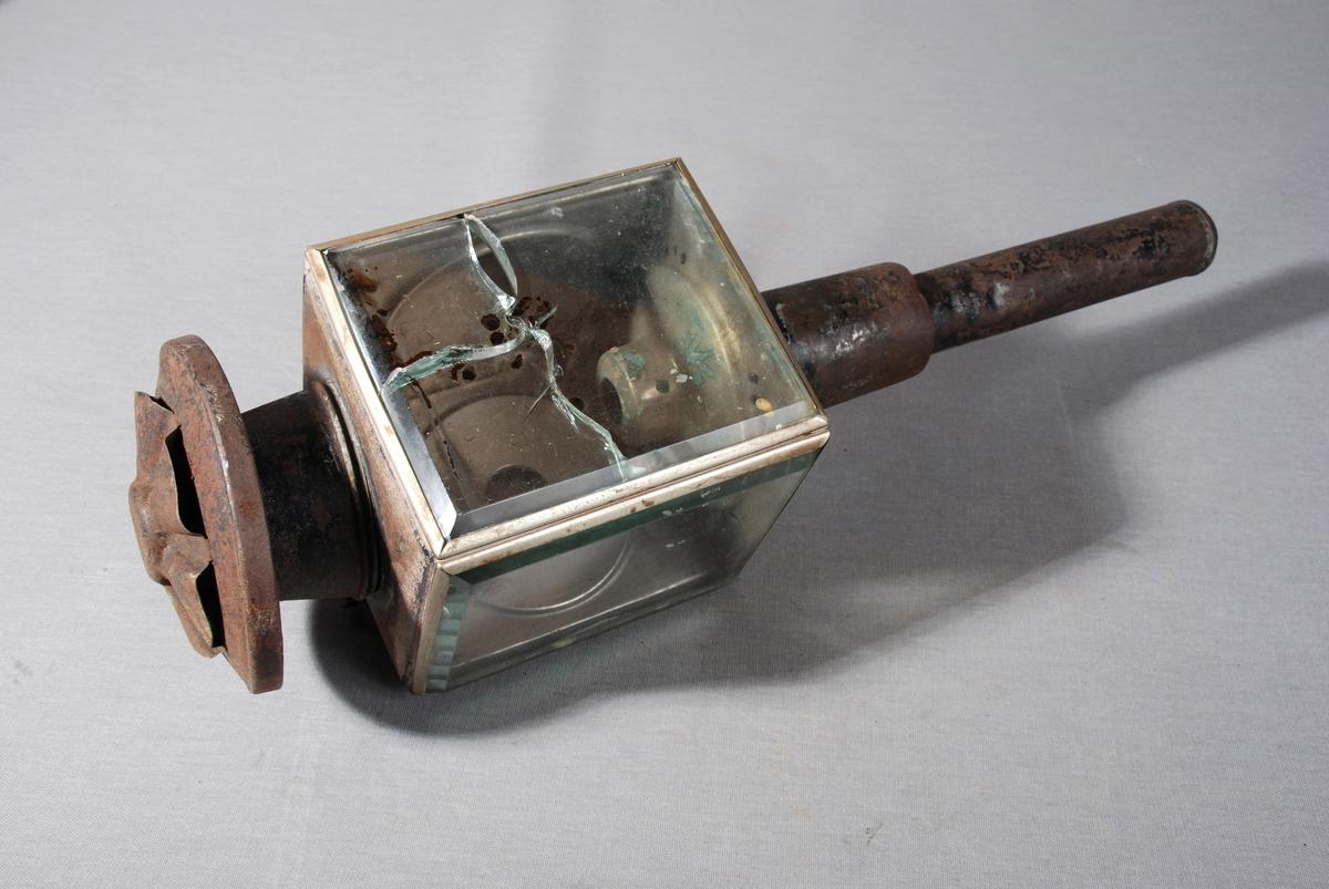Olje-/stearinlyslykt til bruk på hestevogn eller slede. Firkantet lyktehode på metallrør. Øverst hatt for utlufting. Lyktehodet kan åpnes ved at ene siden er hengslet. denne siden har en rund åpning med rødt glass i, omrammet av messingring, En side er av rent metall og to sider er av fasettslipt glass. Innvendig base for brenner.