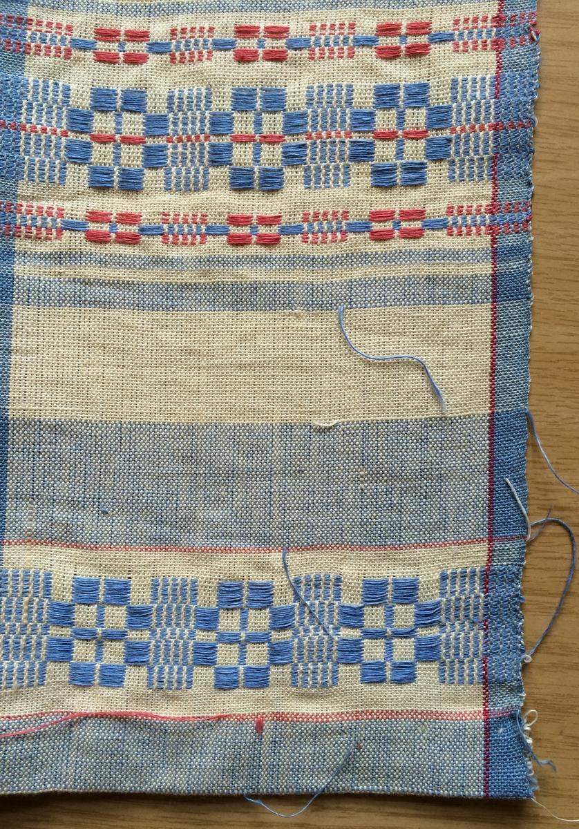 Halvlinnehandduk i munkabälte. Oblekt, mellanblå och röd bomull i varpen och blekt, mellanblått och rött lin i inslaget. Smala och breda ränder i blått och vitt i längdriktningen och munkabältesränder i två olika utförande över bredden. 1,8 cm bred tråcklad fåll. Ingen hank.