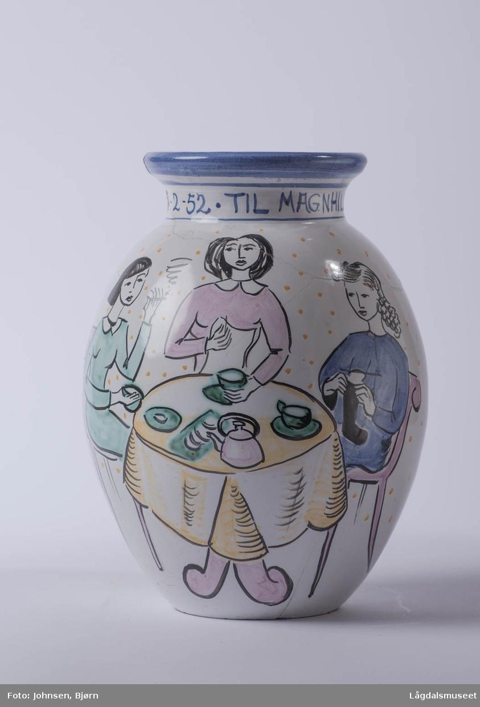 Motivet viser tre damer som drikker te/kaffe rundt et bord. Hun ene strikker, hun andre broderer og hun tredje drikker kun te og prater.