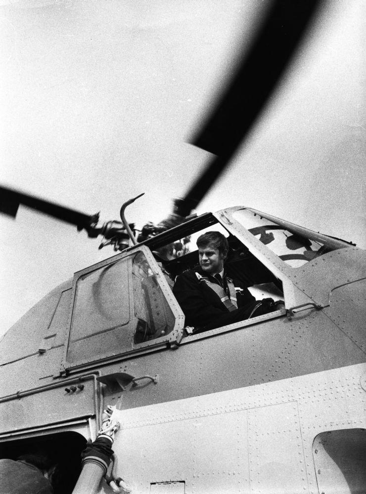 Lufthavn/Flyplass. En person, flyger/pilot, ser ut gjennom en åpen siderute fra cockpit i et helikopter.