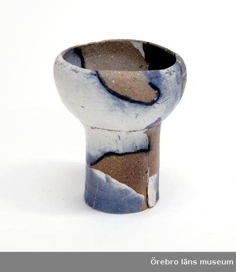 Keramikskål sign B I PÄggformad skål på cylinderformad fot.Gråbrun men med målade fält i vitt, blått och grönt, delvis begränsade av breda mörkblå linjer.Köpt av konstnärinnan på utställning TENN TYG LERA, 5-27 april 1970 på ÖLM för 180:- kr.Neg.nr. 385/71, 386/71