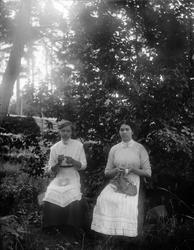 Två kvinnor handarbetar i trädgården, 1910-tal