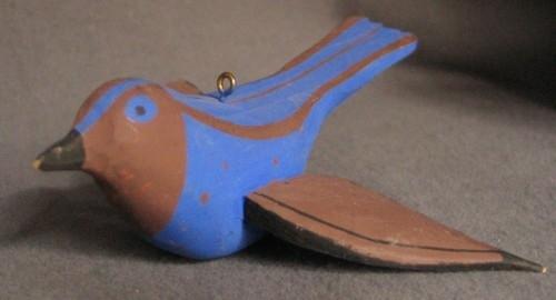 Dekormålad fågel i trä. Hängande fågel med utfällda vingar. Koboltblå med bruna och svarta detaljer.Fågeln är gjord av Sven Dal, Pinkatorparn. Målningen formgiven av Ingrid Dessau. Fåglarna målades av olika kvinnor på bygden.