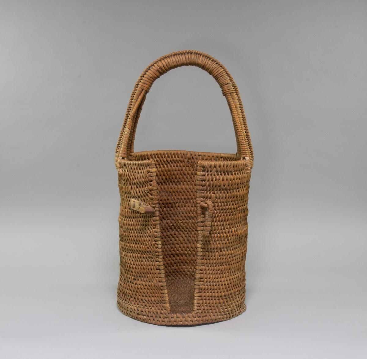 Korg för att bära tallrikar, cylindrisk, flätad av rottågor.  Långsmal öppning i ena sidan, tvärgående tredelad grepe, upptill överklädd till ett grepp. Vid öppningen låsanordning av trä och rottågor, avbruten.