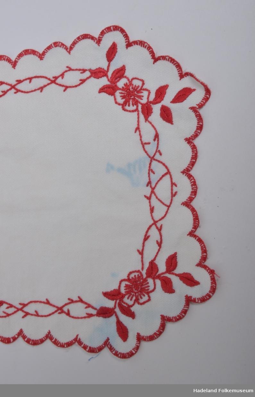 Smekke. Hvitt kypertvevet bomullstoff med broderi og tungestingskant i rødt. Bånd e.lign til å knytte fast smekken med mangler, (aldri montert?) Blå flekk.