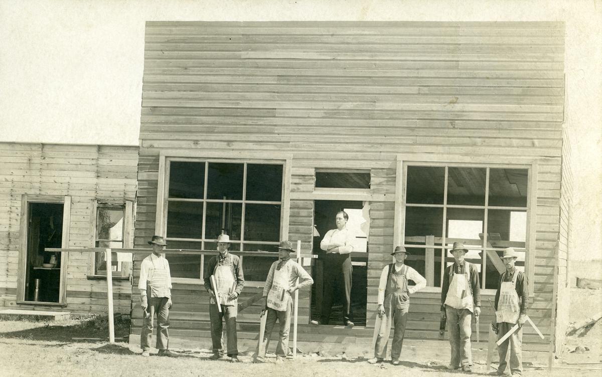 Bildet viser 6 karer i arbeidsklær foran et hus under oppføring.