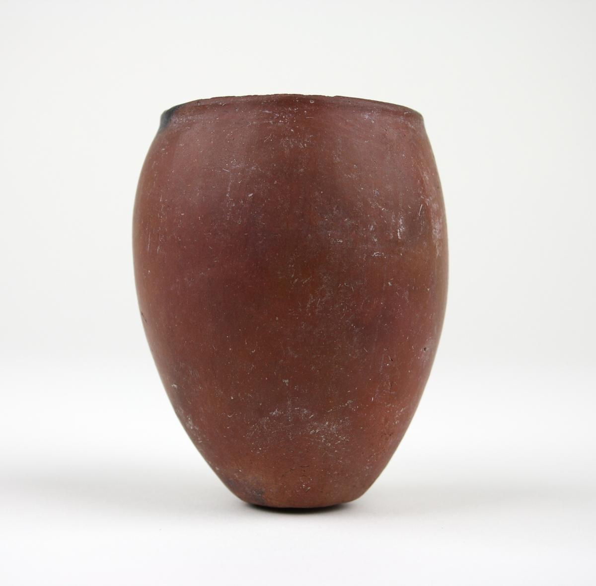 """""""114. Svartrandat kärl. Keramik, höjd 8,5 cm. Förhistorisk tid (Negadeh I och II = före 3000 f. Kr.). Det är främst i Övre Egypten som man hittills funnit dessa svartrandade kärl som är utmärkande för stenkopparålderns senare del. Men även i Nubien och Sudan förekommer svartrandad vara, ofta av yngre datum än den inhemska, egyptiska. Stundom kan det vara svårt att enbart med hjälp av formen avgöra vilket ursprung en svartrandad vas eller skål kan ha.""""  Smithska samlingen av Egyptiska fornsaker i Östergötlands och Linköpings stads museum av Gun Björkman, Meddelanden 1964-1965, s. 105. Mer info om """"Keramik"""" på s. 104."""