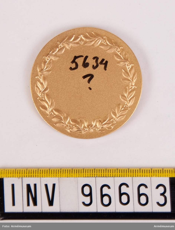 Medalj i guld för Göta trängregemente. Åtsida upptagande rak sköld med lejon på strömmar, krönt av kunglig krona, inom omskrift KUNGL. GÖTA TRÄNGREGEMENTE. Stans nr 14399. Lagerkrans 3377. Stans härdad 1954-05-13.