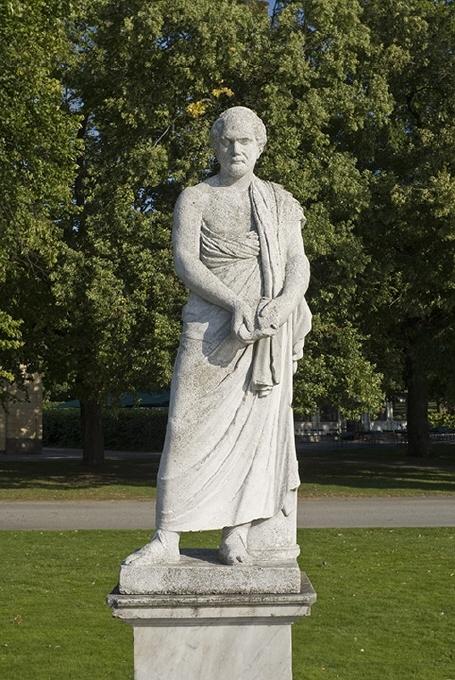 Helfigur stående, huvud fas höger, böjt mot höger axel. I håret månskära. Iklädd kort klänning (kiton), hophållen med ett spänne på vänster axel, skärp om midjan och pilkoger på ryggen. Vilar på det högra benet, det vänstra böjt. Håller högra armen över huvudet, håller med vänster hand en båge, som vilar på en vid hennes vänstra sida sittande hund.