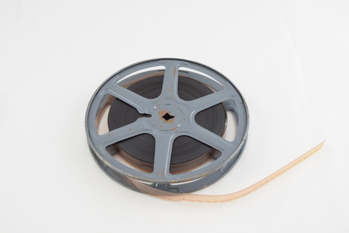 Filmrull i eske. Firkantet papiretui åpnes langs en av sidekantene, festes med lærstropper med metallspenne.