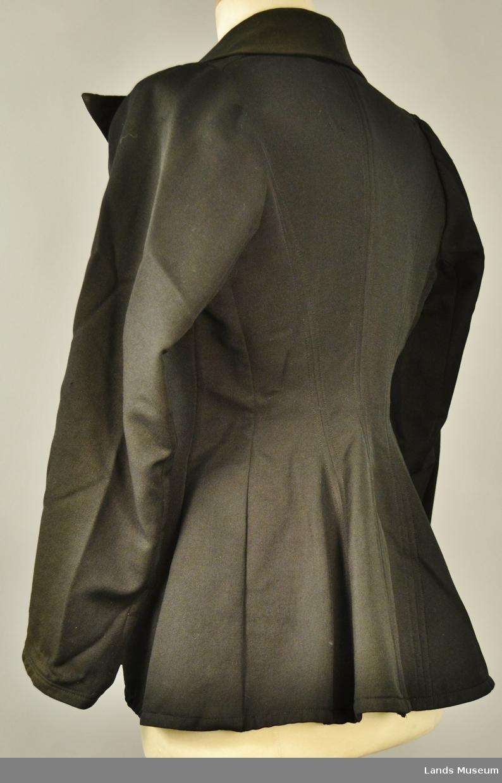 Tre knapper og to lommer. Fine savslutninger på samen på innsida av jakka, kanta med silkebånd. Dobbelsaum på kragen og kanter. Påsydd ei hempe bak i nakken.