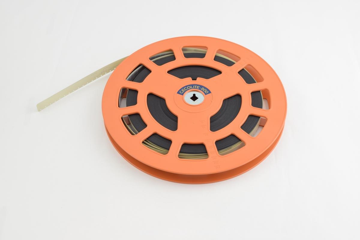 Filmrull i eske. Film på plastspole. Firkantet papir etui åpnes langs en av sidekantene, festes med metallspenne.