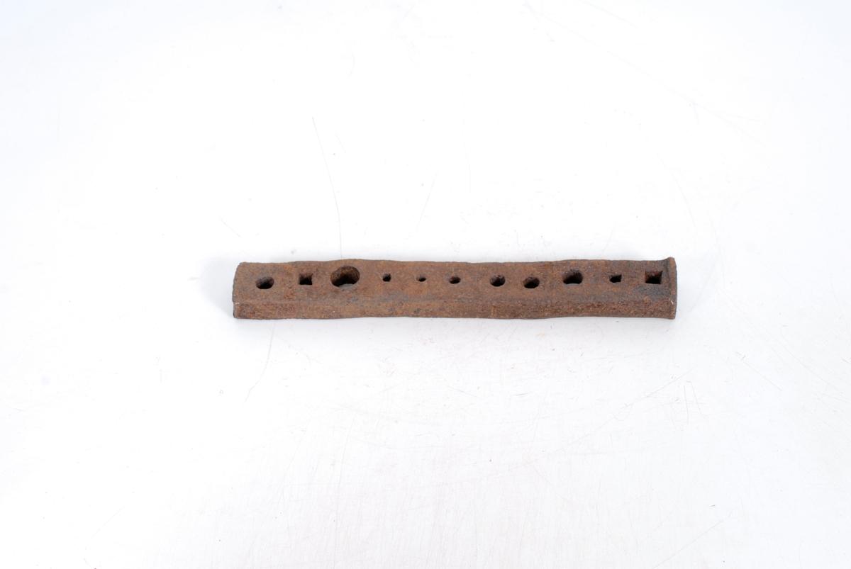 """Form: Rektangulært jernstykke med 11 koniske hol på rad, runde og firkantede. Smedredskap: I ene enden en fortykkelse som kan være resultet av hammerslag, ant. for smiing av bolter, skruer, nagler og søm (reg.). I """"Gamle Danske håndværk""""s 319 nederst er avbildet et lign. redskap som kalles """"naglejern"""", med en serie huller med ulige diametre, bruges til udsmedning af nagle- og sømhoveder i forskjellig størrelse. Fra Årnes i Feiring, gården innkjøpt av kommunen, ting til museet plukket av R.K. I kasse fra smia."""