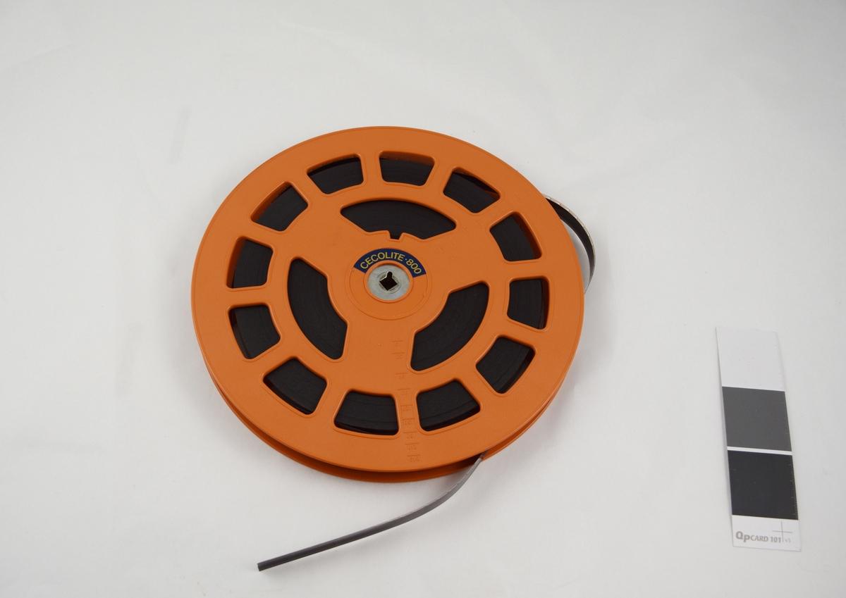 Filmrull i eske. Film på plastspole. Firkantet papiretui åpnes langs en av sidekantene, festes med metallspenne.