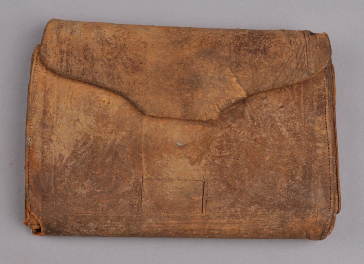 Brun lommebok i skinn. Har fem rom inni og klaff som går rundt desse. På utsida og på eine lommeklaffen inni er det prega akantusmønster.