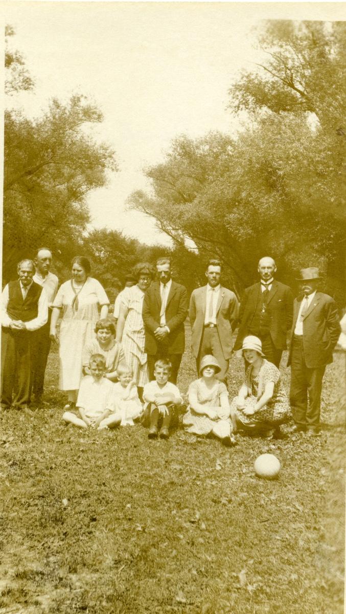 Familiebilde av kvinner, menn og barn. Bildet er tatt i Amerika i 1925.