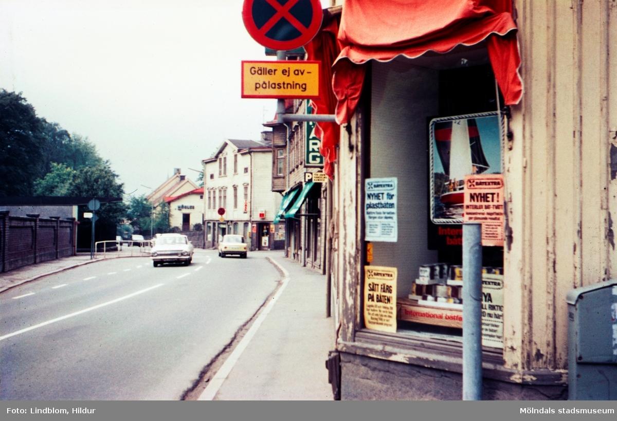 Bebyggelse vid Kvarnbygatan i Mölndal, 1970-tal. På höger sida av gatan ses från höger fastigheterna Kvarnbygatan 27, 25, 23 och längst ned nr 21. På vänster sida Papyrus mur.  För mer information om bilden se under tilläggsinformation.