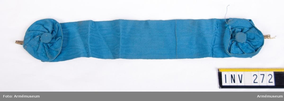 Mellanblått band i vattrat siden, s k moiré. Försedd med hakar i gulmetall att fästas i vaktbrickan, som bäres runt halsen. Som dekoration två st. rundlar sydda av bandet med diameter 55 mm, i mitten försedda med en liten överklädd knapp i moiré.