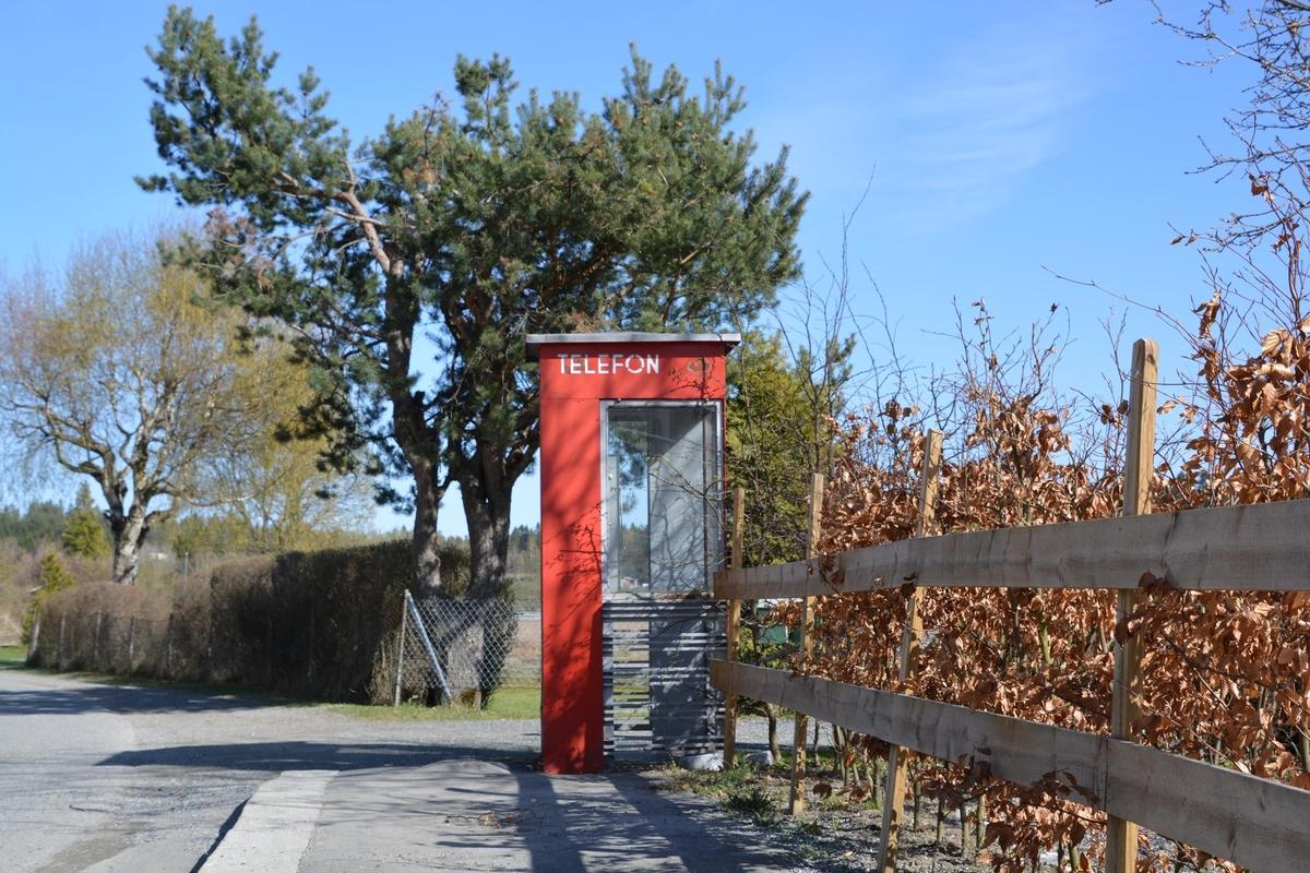 Denne telefonkiosken står i Dronningveien 3 i Hølen, og er en av de 100 vernede telefonkioskene i Norge. De røde telefonkioskene ble laget av hovedverkstedet til Telenor (Telegrafverket, Televerket). Målene er så å si uforandret.  Vi har dessverre ikke hatt kapasitet til å gjøre grundige mål av hver enkelt kiosk som er vernet.  Blant annet er vekten og høyden på døra endret fra tegningene til hovedverkstedet fra 1933. Målene fra 1933 var: Høyde 2500 mm + sokkel på ca 70 mm Grunnflate 1000x1000 mm. Vekt 850 kg. Mange av oss har minner knyttet til den lille røde bygningen. Historien om telefonkiosken er på mange måter historien om oss.  Derfor ble 100 av de røde telefonkioskene rundt om i landet vernet i 1997. Dette er en av dem.