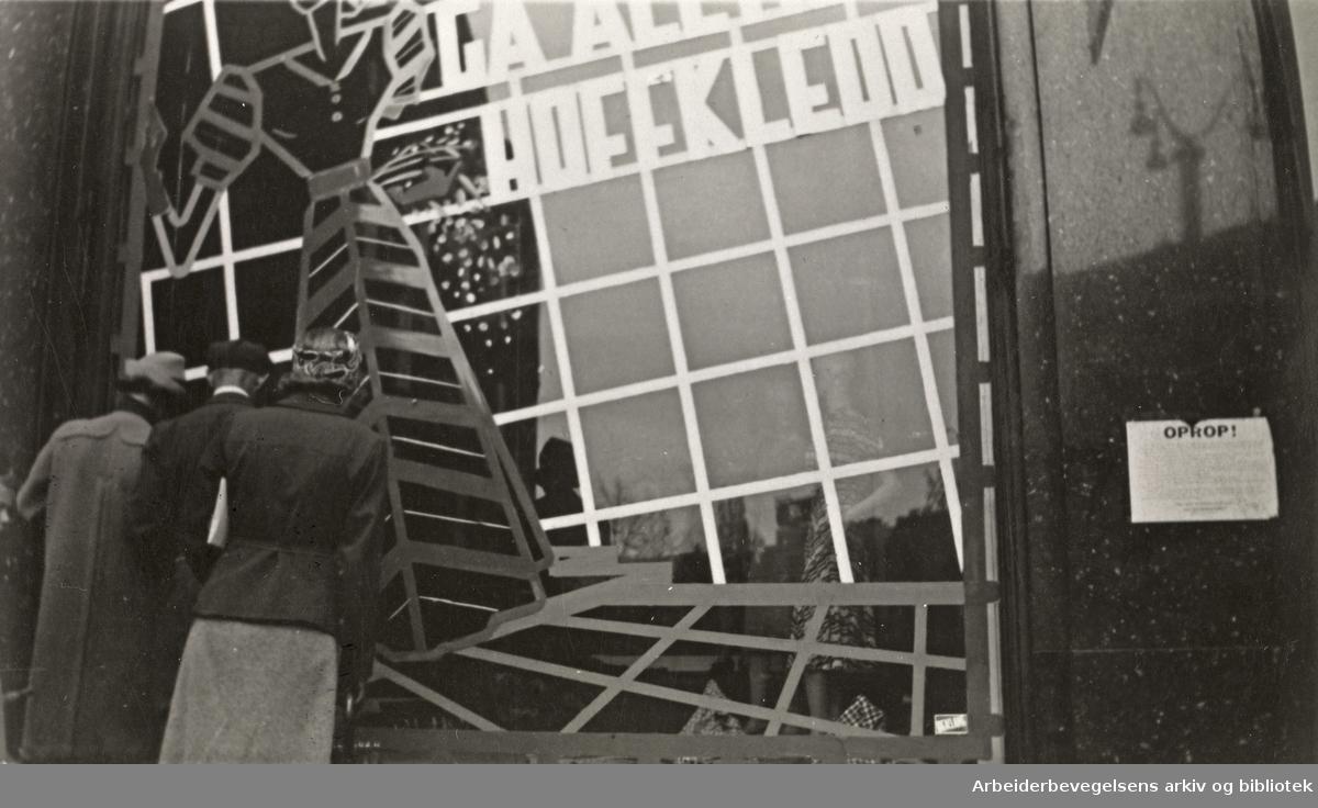"""Ole M. Engelsens fotografier fra okkupasjonsårene i Oslo. Slik ble vindusrutene sikret for å hindre at glasset skulle splintres ved flyangrep. .""""Gå alltid Hoffkledd""""..Bildet er tatt utenfor Hoff damekonfeksjon i Karls Johans gate 25, mai 1940."""