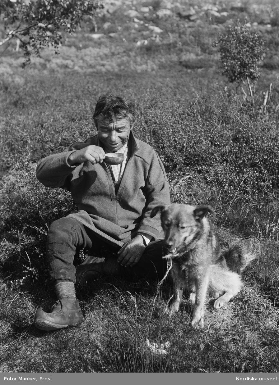 Mickel Pannasson Skano, same av gammal Sörkaitumsläkt sitter i gräset och dricker ur en kåsa. Vid hans sida sitter en hund.