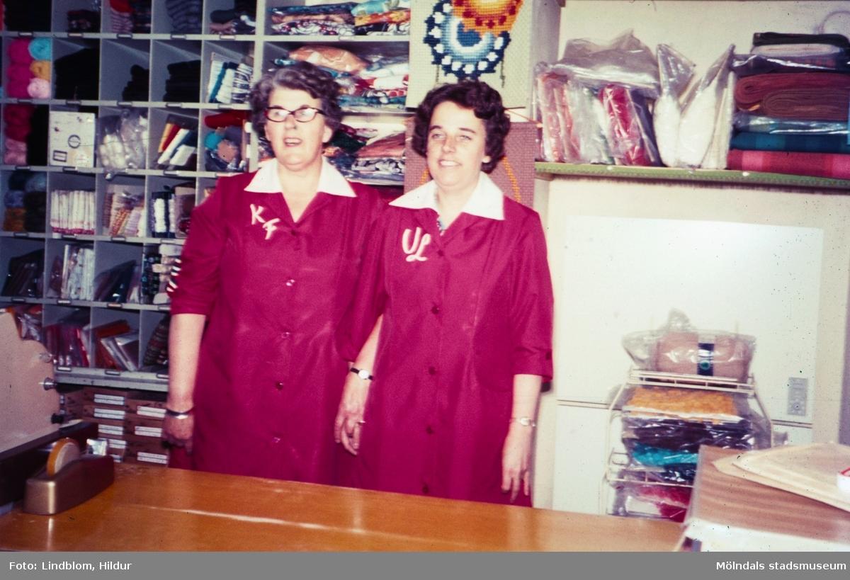Två kvinnor fotograferade vid kassan i Kvarnbyns garn och handarbetsaffär med adress Kvarnbygatan 37 i Mölndal, 1970-tal. Till vänster ses Kajsa som var ägare av garnaffären och till höger Ulla, som senare kom att arbeta i Rasmussons skoaffär.  För mer information om bilden se under tilläggsinformation.