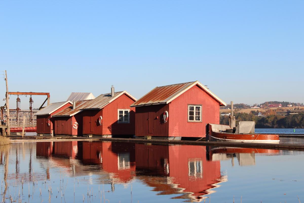 Fire røde hvilebrakker som ligger i elva med en liten bår i forgrunnen (Foto/Photo)