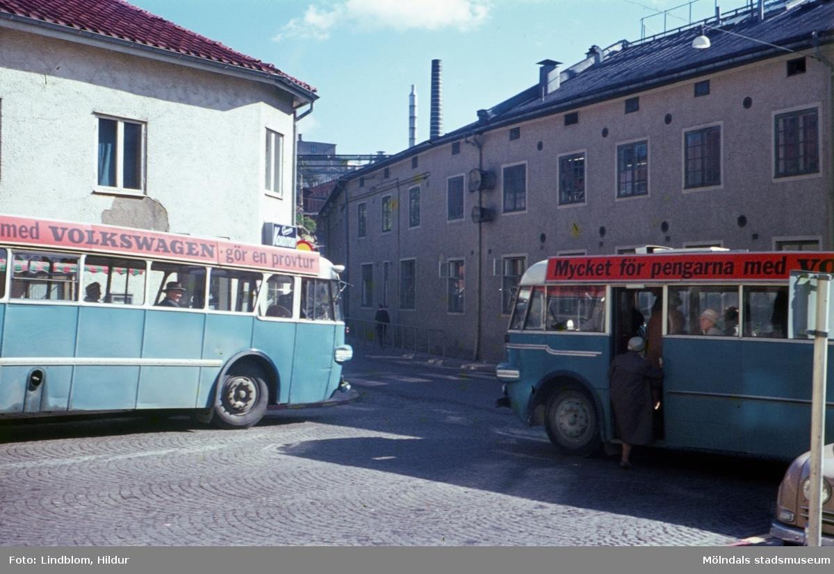 Två blå bussar står på Gamla Torget i Mölndal, 1960-tal. I bakgrunden till vänster ses huset Kvarnbygatan 45 och till höger Kvarnbygatan 6, byggnad tillhörande SOAB.  För mer information om bilden se under tilläggsinformation.