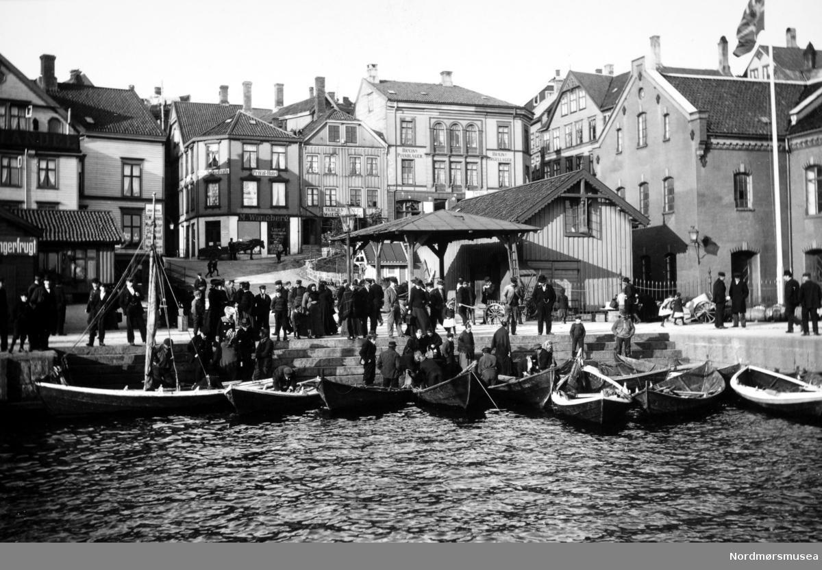 """Foto fra Fisketrappa ved Fisketorget på Kirkelandet i Kristiansund, hvor vi ser stor aktivitet av folk som er interessert i å kjøpe fersk fisk fra fiskerne som har lagt til ved trappen. Ellers så ser vi noe av bebyggelsen i bakgrunnen, med blant annet litt av Loennechens bokhandel helt i front til venstre. Deretter ser vi butikken til M. Wangberg med privat-hotell i 2.etg. Neste forretning er Peder """"?"""" kolonialforretning, fulgt av Bræins piano- og orgellager. I front til høyre ser vi til slutt Tollboden med lager. Fotograf og datering er ukjent, men trolig er datering omkring 1910 til 1930. Fra Nordmøre Museums fotosamlinger."""