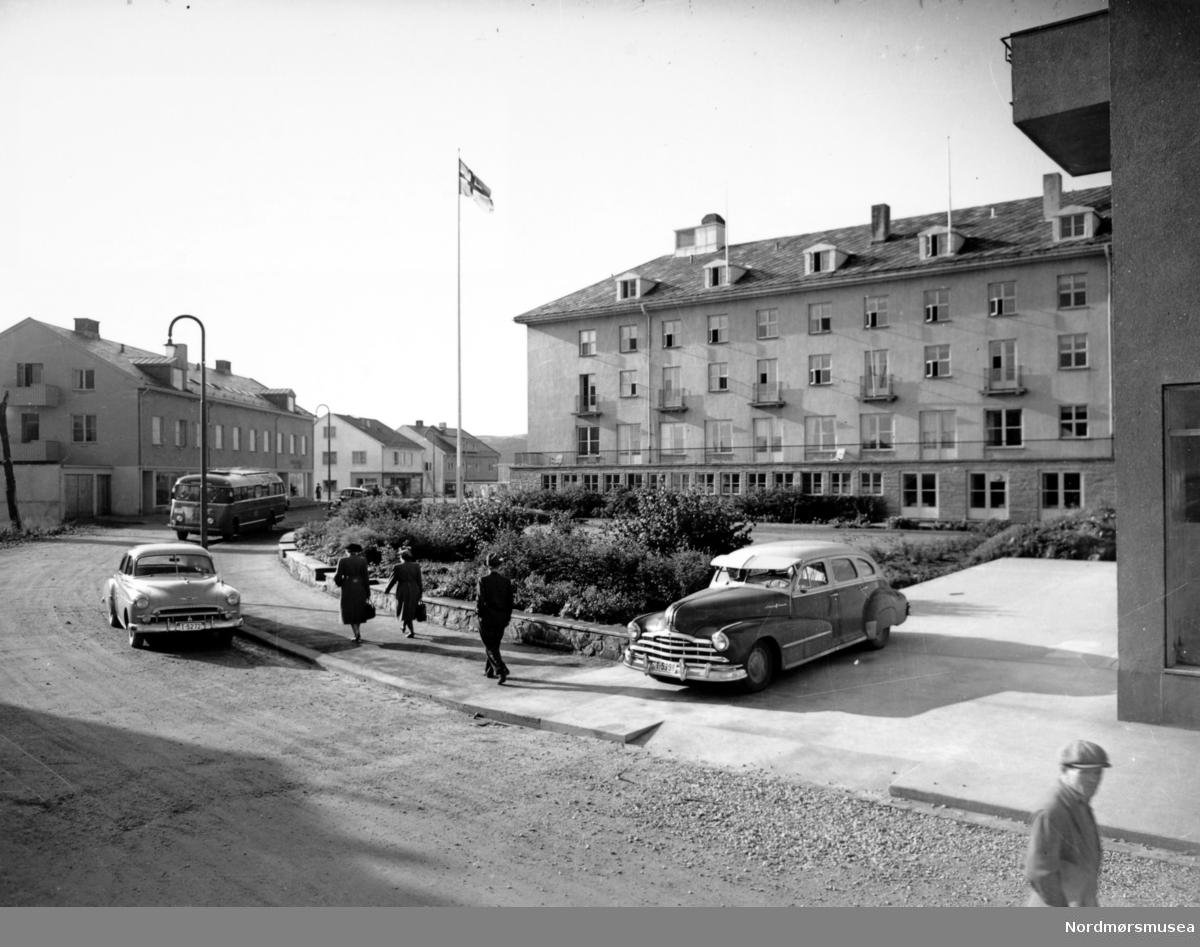 Storgata 13 er ennå ikke bygd, Storgata er grusvei!  Et bilde av byens tredje Grand Hotell med Knudtzonhagen i Bernstorff-stredet, sett fra Storgata.   Etter at byens andre Grand Hotell ble satt i brann i aprildagene 1940 og tyskerne tok over byen, ble det raskt bestemt at hotellet skulle bygges opp igjen. Dette skyldtes utvilsomt tyskernes prekære behov for et hotell.  Tomten ble ryddet og stod klar i 1941, og i juli samme år døde eieren av Grand Hotell Nils Nilsen. Hans nærmeste arvinger Elise og Esther Nilsen overdro senere i januar 1942 eiendommen Torvet 7 til A/S Grandgården, som da hadde fått godkjent anmeldelse av nybygg.  Mens det første Grand Hotell ble bygd i Sveiterstil og byens andre ble bygd i en nøktern variant av jugendstil, ville det tredje hotellet, som nå ville bli oppført med moderne materialer, bli reist i en kombinasjon av nyklassisisme og funksjonalisme.   Entreprenøren av det tredje Grand Hotell var A/S Vestlandsbygg og byggherre var Konsul Odd Blom Nielsen, innehaver av Jernvarefirmaet Ingwald Nielsen i Oslo, på vegne av A/S Grandgården. Arkitekten bak bygget var Hugo A. Brustad, Oslo  Torsdag 21. mai 1942 stod nybygget klart, og det ble slått stort opp at hotellet ville bli åpnet i løpet av september-oktober. Dette skjedde ikke da flere uforutsette hendelser dukket opp, men 27. februar 1943 slo avisene opp at Grand stod nå i disse dager klart til å taes i bruk. Komplekset ble 58 meter i lengden og 14,5 meter i bredden, og alt i alt fikk hotellet 67 gjesterom.  Flere endringer skjedde i de kommende årene. Restaurantdriften var en av dem. Den 8. mai 1951 ble Palmetten åpnet, etterfulgt senere av etableringen av Gripsalen i den gamle Grandkjelleren. I denne kom det nå inn flotte malerier utført av Einar Granum og Tidens Krav kunne lørdag 19. september 1953 melde om at Vi har fått en Gripssal i Kristiansund.  Ved generalforsamlingen 24. juni 1970 ble det lagt frem et forslag om et tilbygg på 70 rom. Ulempen her var at utvidelsen var tiltenkt der