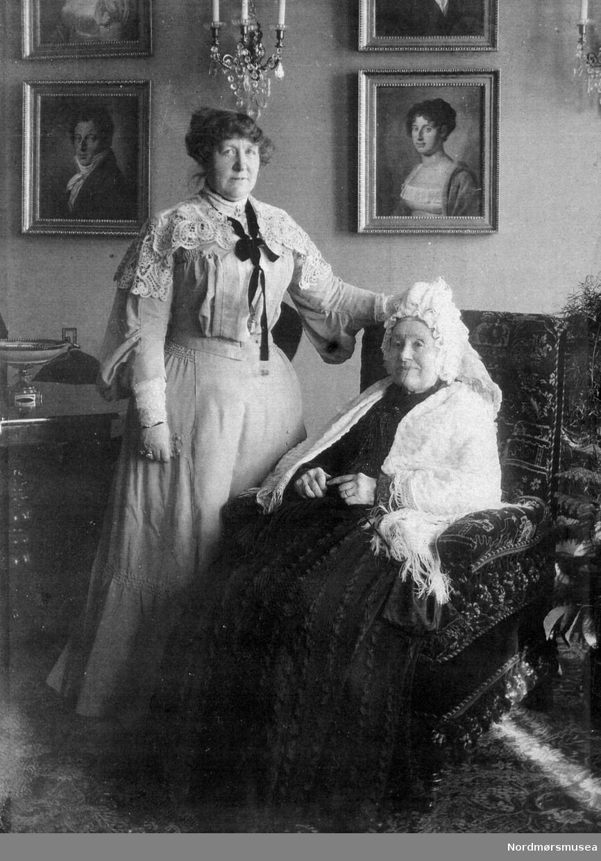 Fru Caroline Nathalie Werring (f.1849 -d . 1935), gift Knudtzon, sammen med sin mor fru dr. Werring, fotografert i salonen i Knudtzongården. Bildet er gitt av Dea Yderstad, født Aas, - fra hennes foreldres familiealbum (politimester Aas med frue, født Boye). Datering er fra slutten av 1890 årene. ALTØ: Portrettene på veggen bak til venstre er: Peter Christian Knudtzon f. 1789- d. 1864., gift 1. gang med Marie Thomsen f. 1788- d. 1831, gift andre gang med Lucinde Gottschalk f. 1818- d. 1888. Pastell av Christian Hornemann. Til høyre på veggen: Marie Magdalene Knudtzon f. 1786- d. 1872. Hun var gift med soknepres, Kvernes, stiftsprost Lorentz Angell . Pastell av Christian Hornemann. Fra Nordmøre Museums fotosamlinger. dublett
